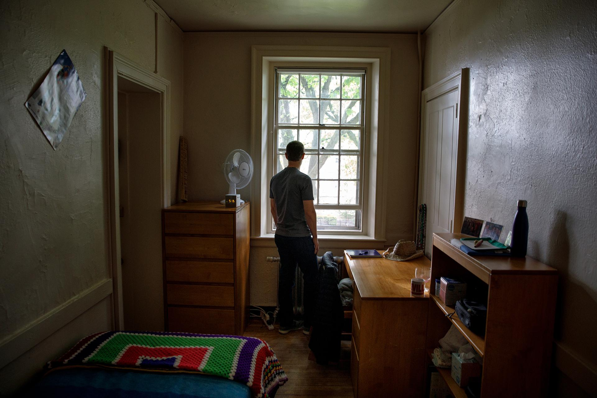 In this Tuesday, May 23, 2017, photo, provided by Facebook, CEO Mark Zuckerberg looks out the window in his old dorm room at Harvard University, in Cambridge, Mass. Zuckerberg started Facebook in his dorm room in 2004, and also met his wife, Priscilla Chan, at Harvard. On Thursday, May 25, Zuckerberg will give the commencement address at the university, where he dropped out 12 years earlier to focus on Facebook. (Courtesy of Facebook via AP)